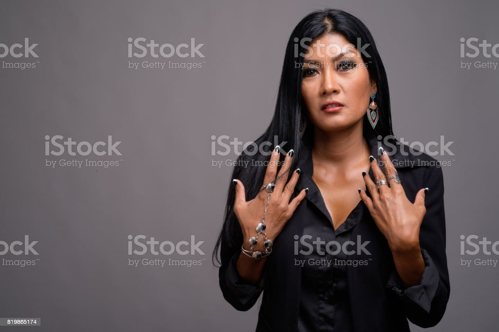 Studio shot of beautiful Asian businesswoman against gray background stock photo
