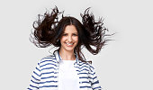 istock Studio shot of beautiful joyful brunette woman with flying hair smiling broadly, looking directly at the camera, posing over white background. People real emotions 1140342494