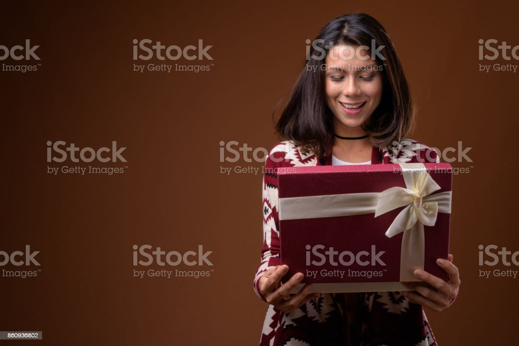 Studio shot of beautiful multi-ethnic woman holding gift box ready...