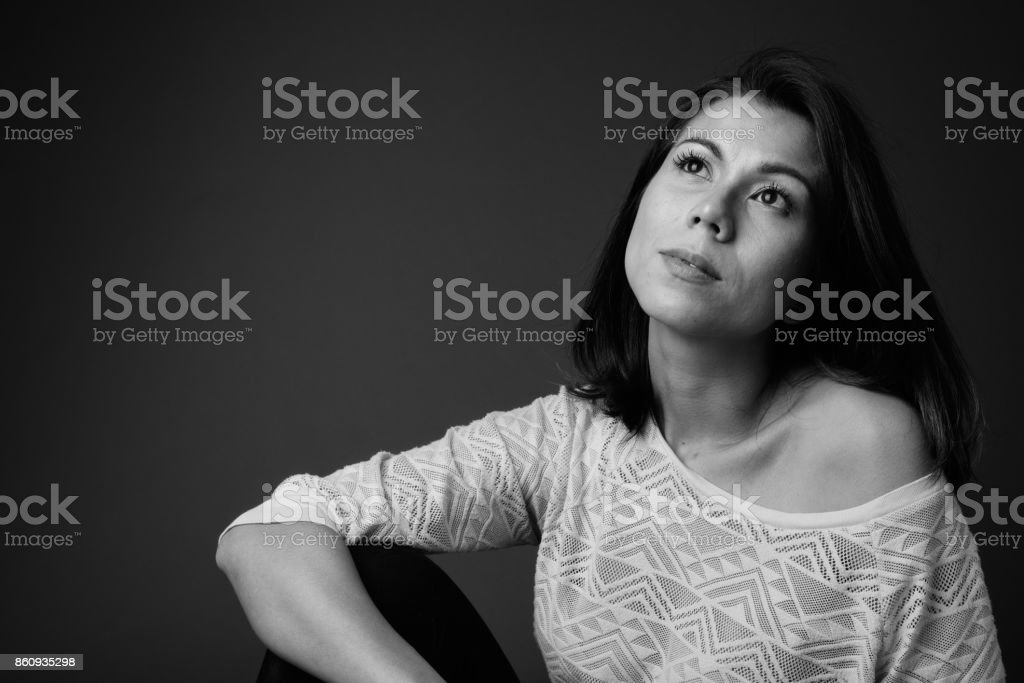 Studio shot of beautiful multi-ethnic woman with short hair against black background stock photo