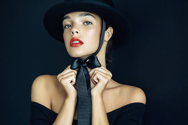 studio shot of beautiful woman wearing black hat - knotenkleid stock-fotos und bilder