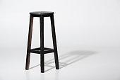 istock Studio shot of classic black tall wooden barstool standing on white 827667992