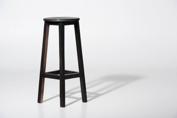 Studio shot of classic black tall wooden barstool standing on white Studio shot of classic black tall wooden barstool standing on white stool stock pictures, royalty-free photos & images