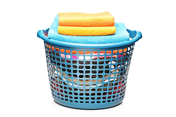 Studio shot of colorful towels in a laundry bin A studio shot of colorful towels in a laundry bin isolated on white background laundry basket stock pictures, royalty-free photos & images