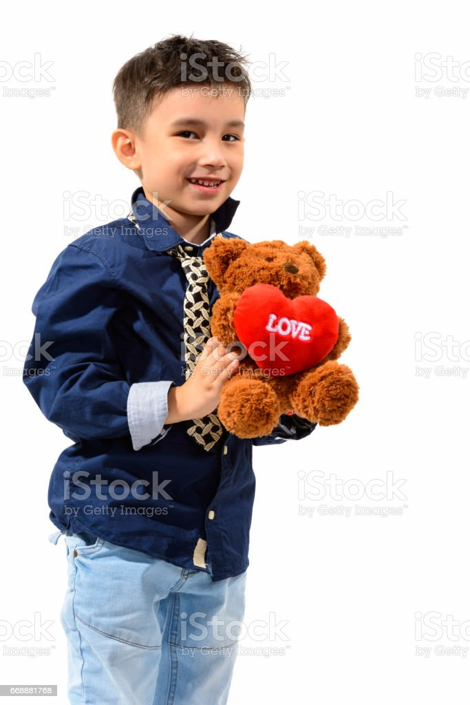 Studio shot of cute happy boy smiling and looking at camera while holding teddy bear with heart and love sign stock photo