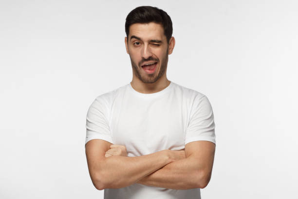 Studio shot of good looking man isolated on grey background looking enterprising and enthusiastic, winking friendly as if inviting to adventure or recommending good benefit stock photo
