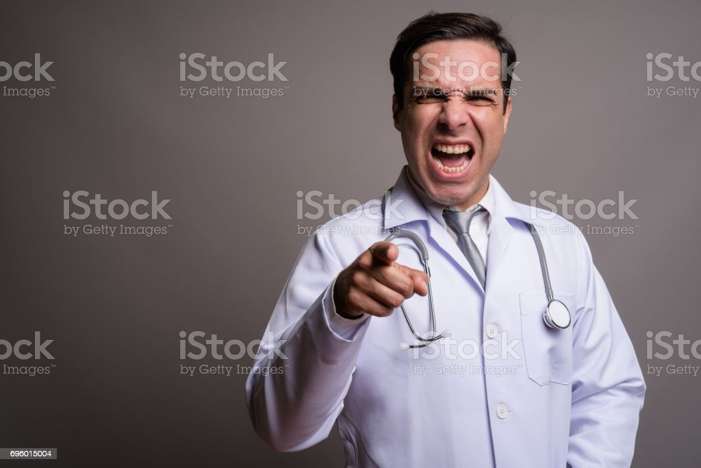 Studio shot of handsome Persian man doctor against gray background stock photo