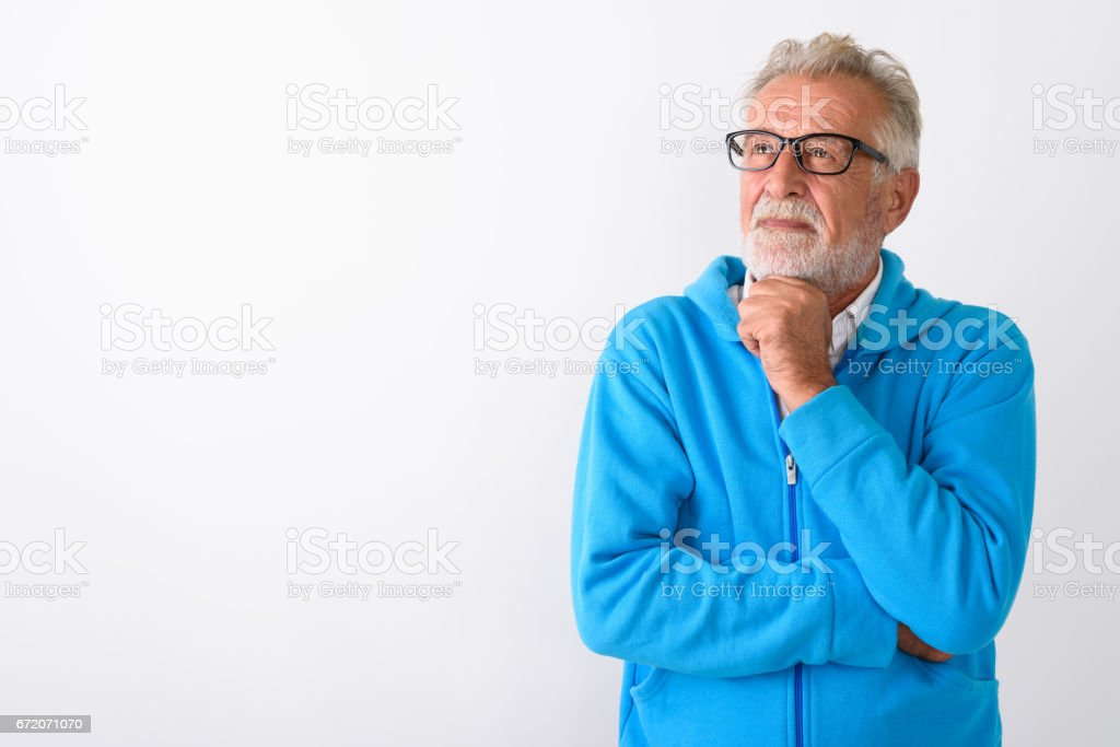 Studio shot of handsome senior bearded man thinking while looking up ready for gym against white background Studio shot of handsome senior bearded man thinking while looking up ready for gym against white background horizontal shot 60-64 Years Stock Photo