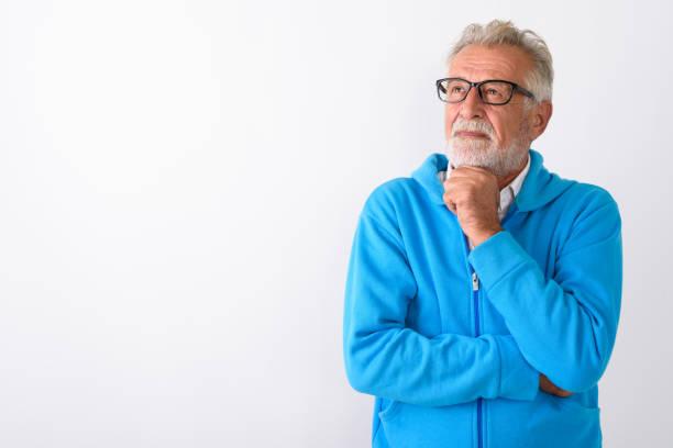 studioaufnahme von schöner senior bärtigen mann denken beim nachschlagen bereit für fitness-studio vor weißem hintergrund - einzelner senior stock-fotos und bilder