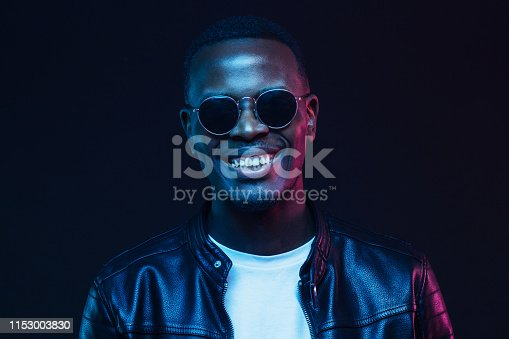 1095939686istockphoto Studio shot of handsome smiling african american male model wearing trendy sunglasses and leather jacket 1153003830