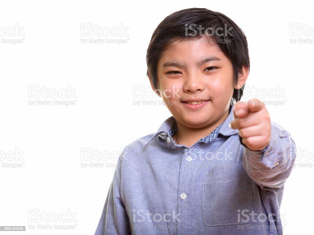 ニコニコと人差し指のカメラで満足しているかわいい日本少年のスタジオ