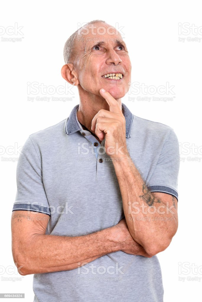 Studio shot of happy senior man smiling while thinking stock photo