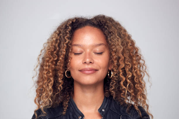 studio shot of happy young woman with eyes closed daydreaming - augen geschlossen stock-fotos und bilder