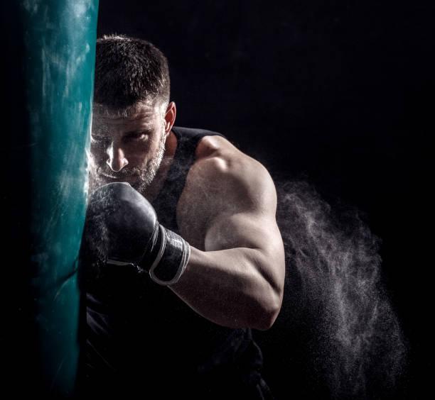 studioaufnahme von männlichen boxer stanzen ein boxsack. - sandsäcke stock-fotos und bilder