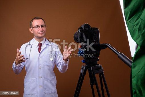 Studio shot of man doctor wearing eyeglasses while vlogging against colored background horizontal shot