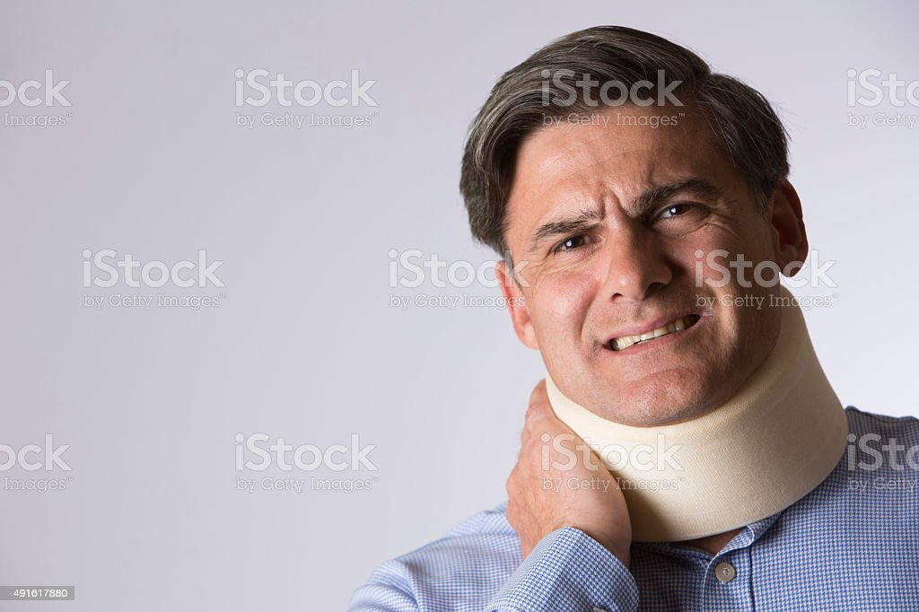 Studio Shot Of Man In Pain Wearing Neck Brace stock photo