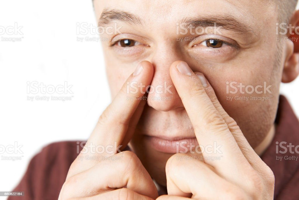 Studio Shot Of Man Suffering With Sinus Problem stock photo