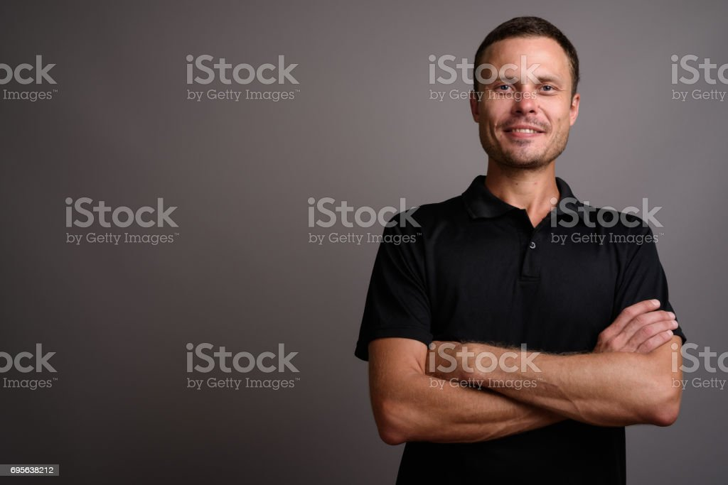 Studio shot of man wearing black polo shirt against gray background stock photo