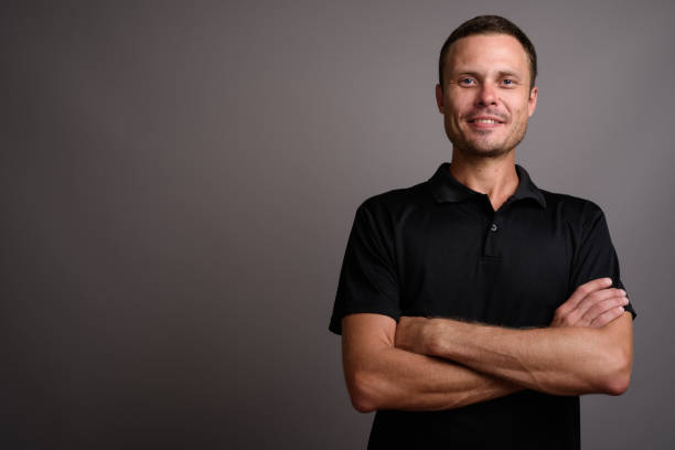 Studio shot of man wearing black polo shirt against gray background stock photo