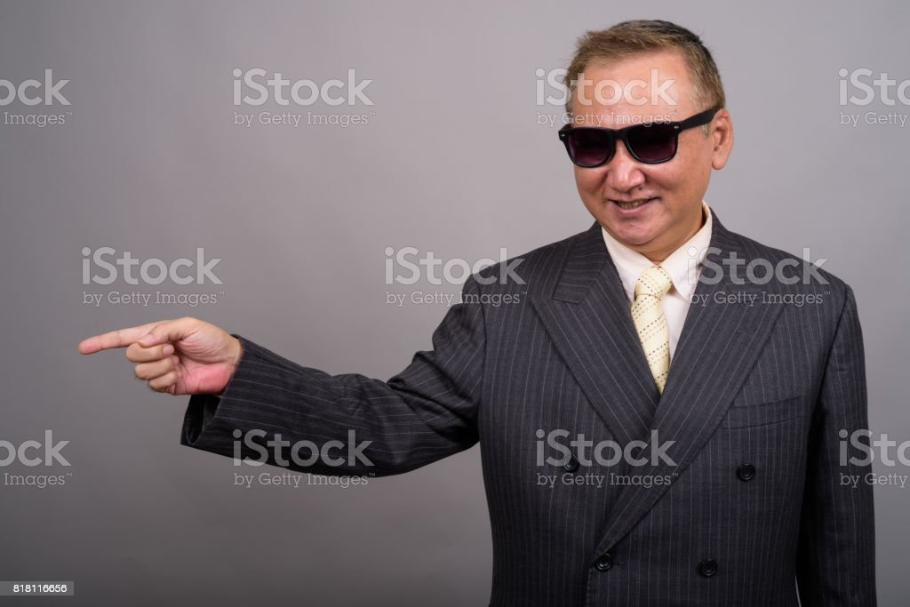 Studio shot of mature Asian businessman wearing sunglasses looking cool against gray background stock photo