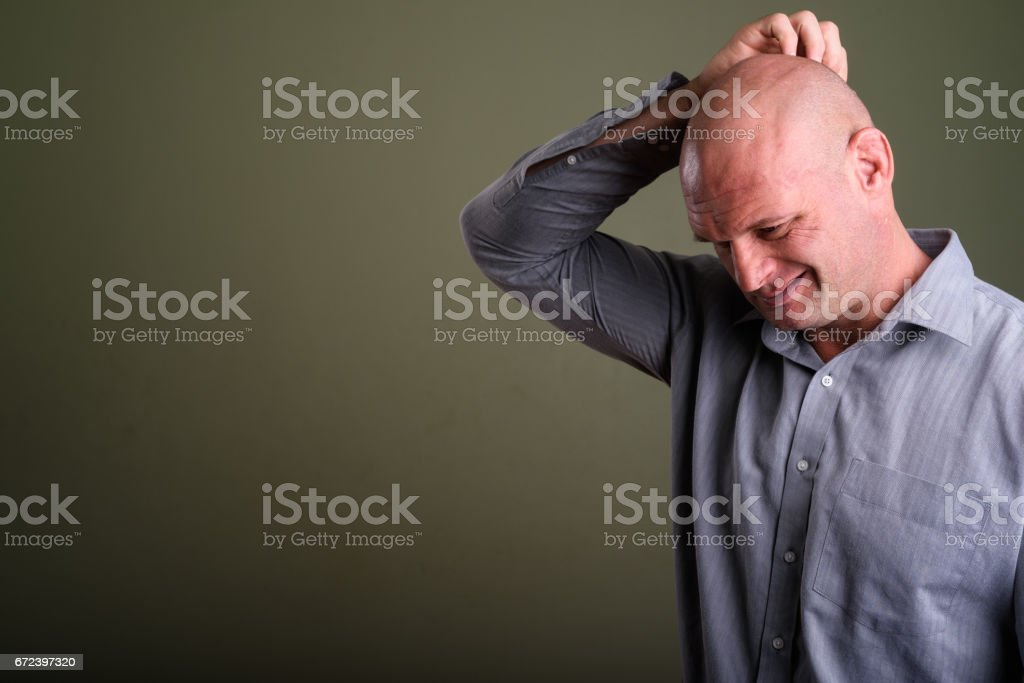 Studio shot of mature bald muscular businessman against colored background stock photo