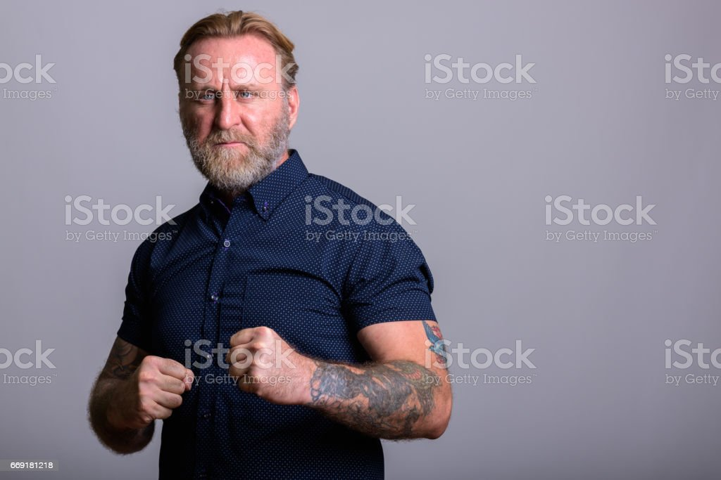 Studio shot of mature bearded man with hand tattoos getting ready to fight in gray background stock photo