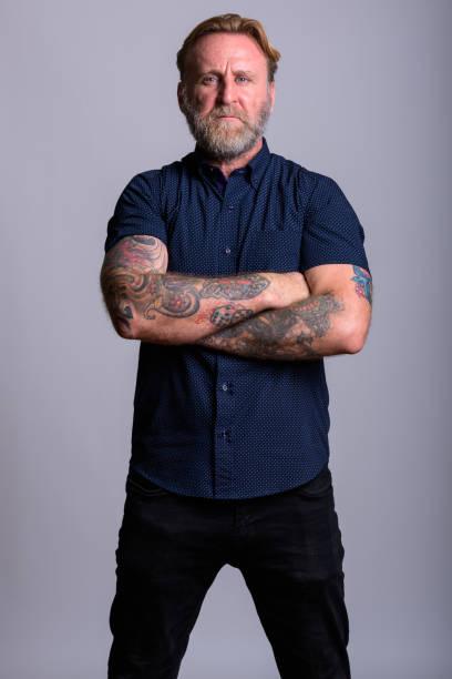 studioaufnahme von reifen bärtigen mann mit hand tattoos stehen mit verschränkten in grauen hintergrund - mann bart freisteller stock-fotos und bilder