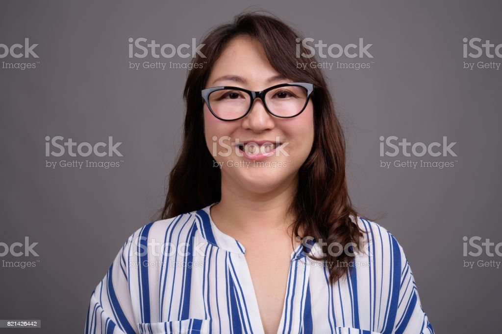 Studio shot of mature beautiful Asian businesswoman against gray background stock photo