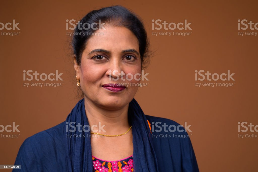 Studio Shot Of Mature Beautiful Indian Woman Against Colored Background Stock Photo
