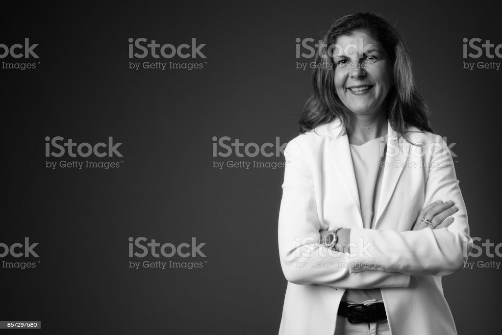 Studio shot of mature businesswoman wearing pant suit against gray background stock photo