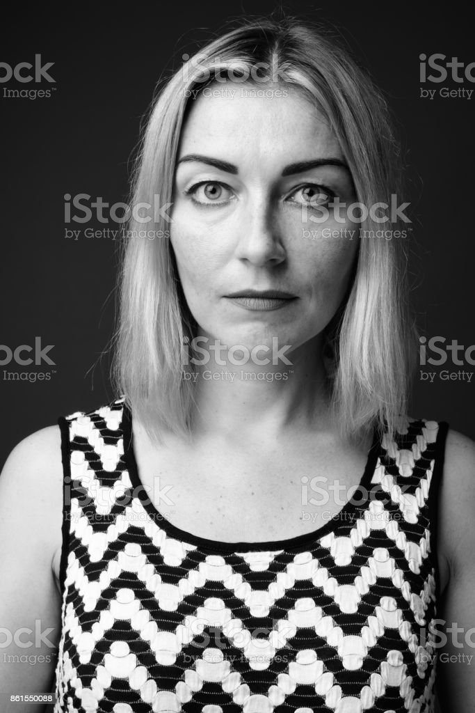 Studio shot of mature businesswoman wearing zigzag patterned sleeveless dress in black and white stock photo