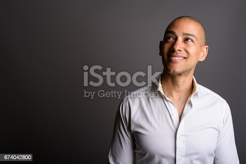 istock Studio shot of mature handsome bald businessman against gray background 674042800