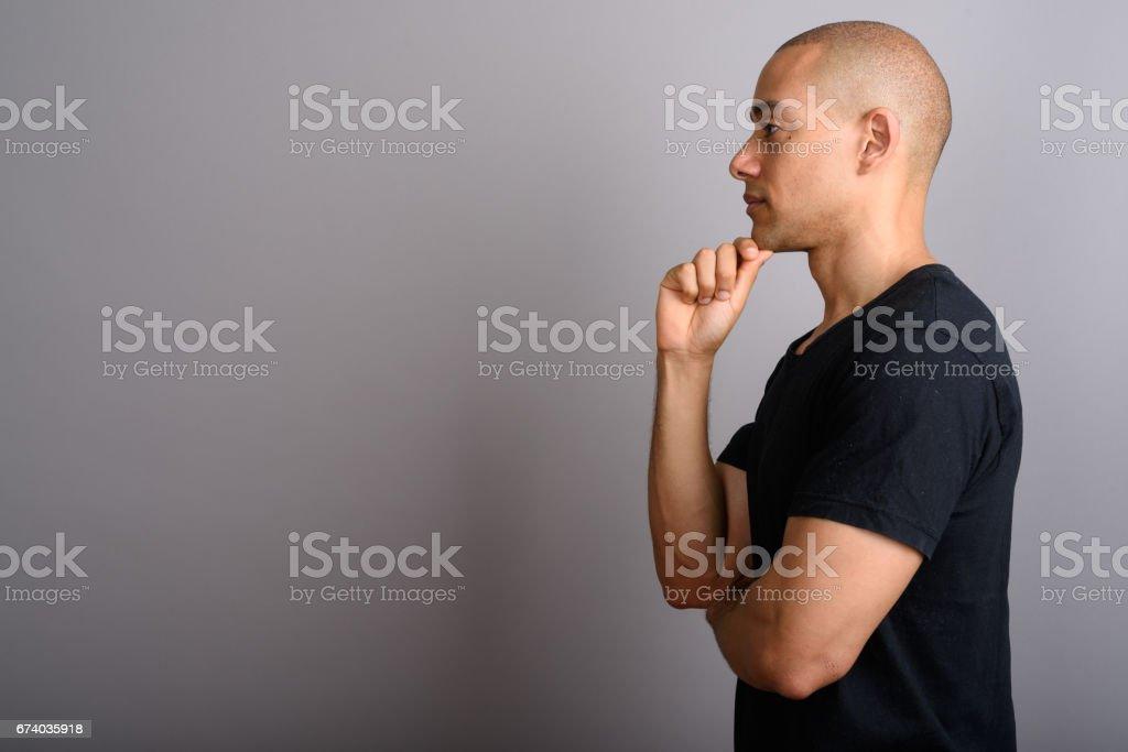 Studio shot of mature handsome bald man against gray background stock photo