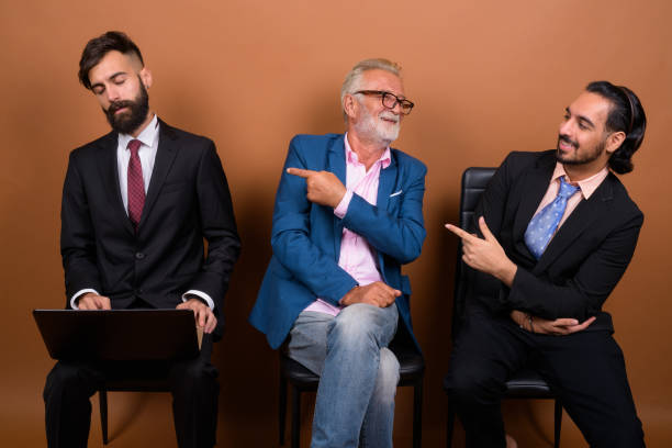 Studio shot of multi ethnic group of three bearded businessmen waiting for an interview together against colored background stock photo