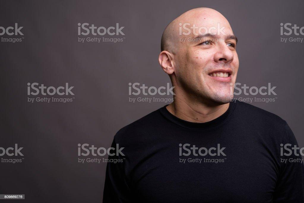 Studio shot of muscular bald man wearing black shirt against gray background stock photo
