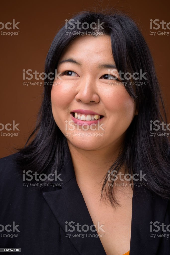 Studio shot of overweight Asian businesswoman against colored background stock photo