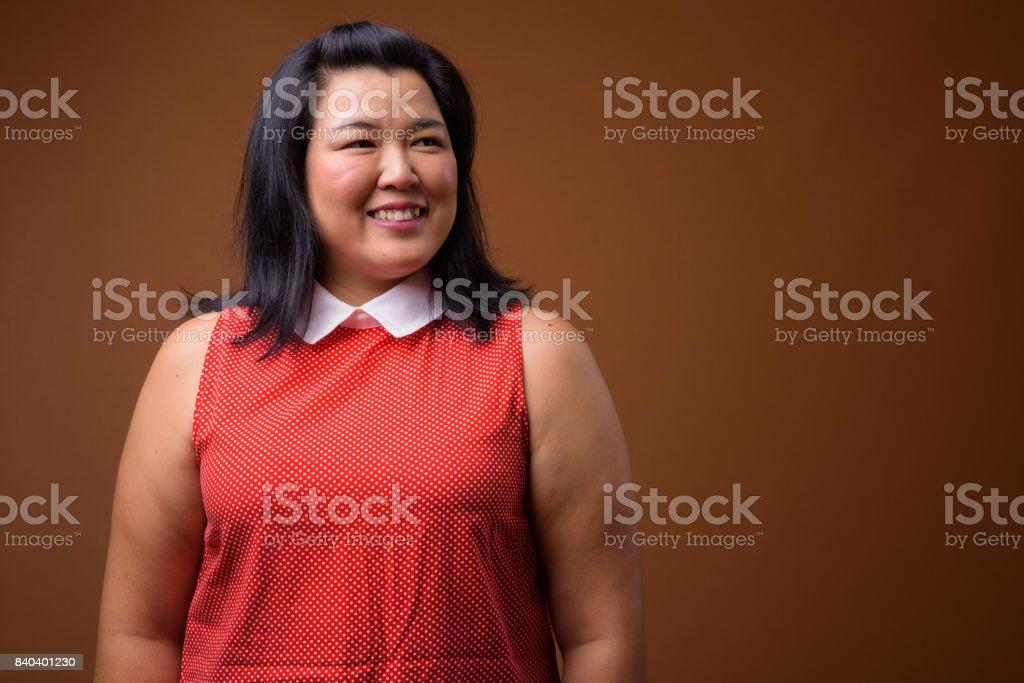 工作室拍攝的超重亞洲女人穿著彩色背景的紅色衣服圖像檔