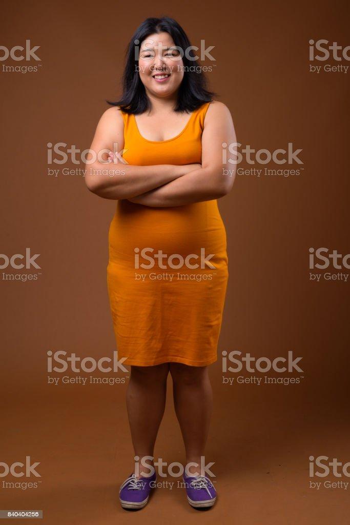 工作室拍攝的超重亞洲女人穿著黃色橙色穿彩色背景圖像檔