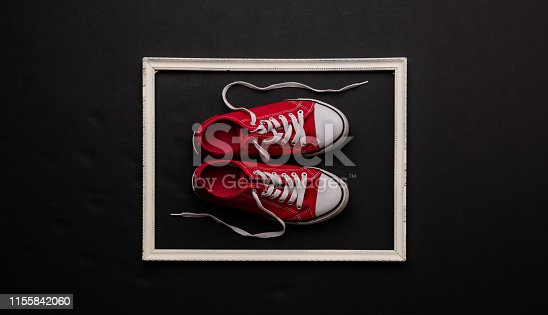 A studio shot of pair of modern canvas shoes on black background. Flat lay, top view.