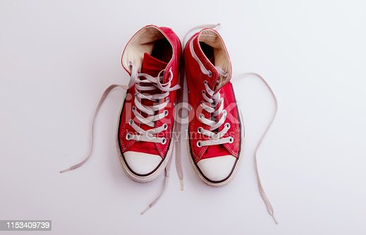 A studio shot of pair of modern canvas shoes on white background. Flat lay, top view.