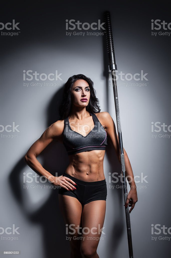 studio shot of perfect body of bodybuilder female with barbell; royaltyfri bildbanksbilder