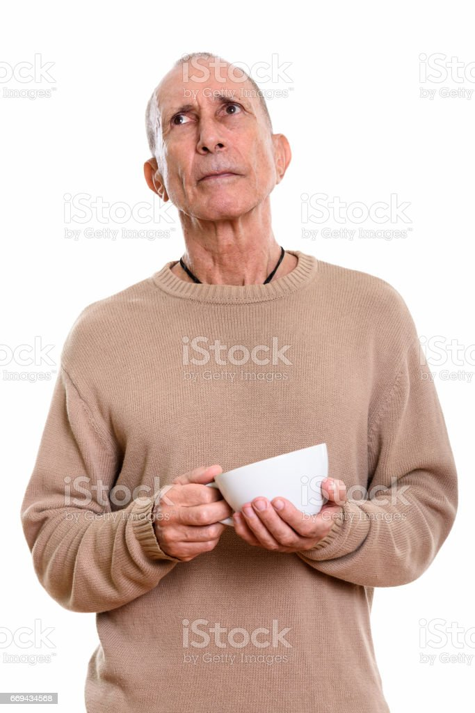 Studio shot of senior man holding coffee cup while thinking stock photo