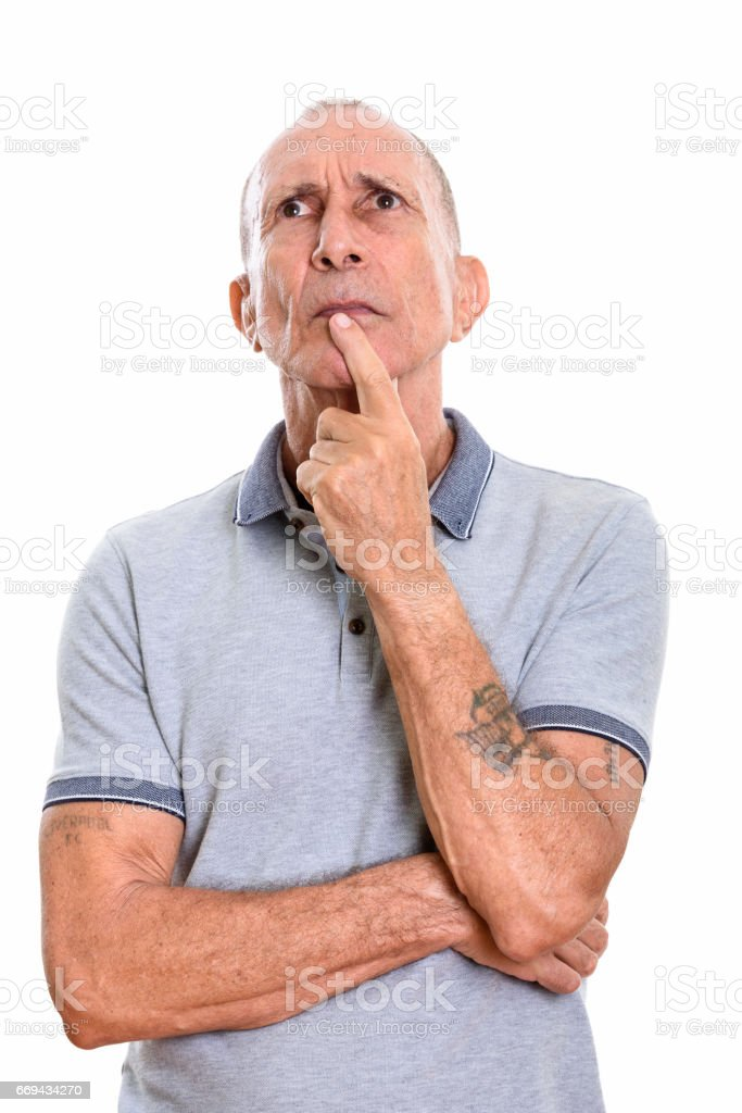 Studio shot of senior man thinking while looking up stock photo
