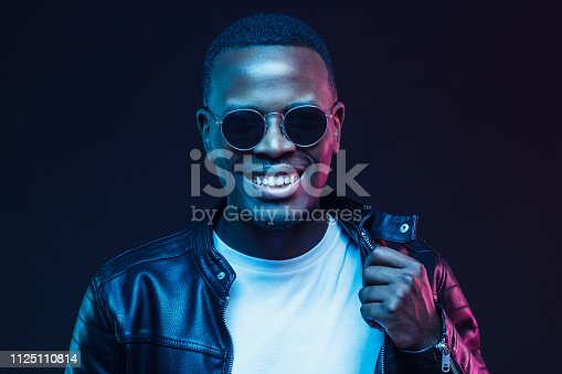1095939686istockphoto Studio shot of smiling african american male model wearing trendy sunglasses and leather jacket 1125110814
