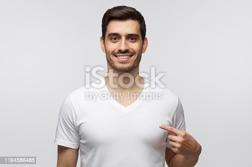 1018069806 istock photo Studio shot of smiling young man pointing at his blank white t-shirt with index finger, copy space for your ads, isolated on gray background 1164586485