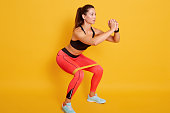 Studio shot of sporty woman squatting, doing sit ups with resistance band. Photo of Caucasian woman in fashionable sportswear isolated over yellow background. Strength and motivation concept.