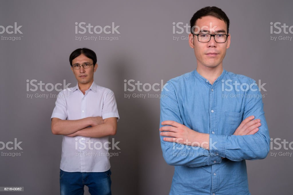 9e5066e56cba Studio shot of two young Asian businessman wearing eyeglasses together against  gray background royalty-free
