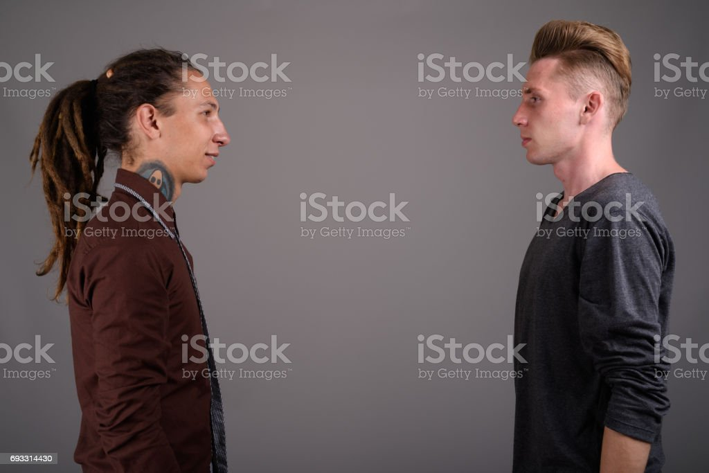 Studio shot of two young man friends against gray background stock photo