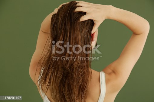 istock Studio shot of woman applying hair oil with her fingers 1175291197