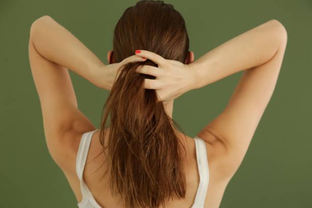 Studio-Aufnahme der Frau, die Haaröl mit ihren Fingern auftragen – Foto